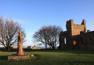Lindisfarne Priory with castle in background - credit: Gail Johnson, Visit Northumberland